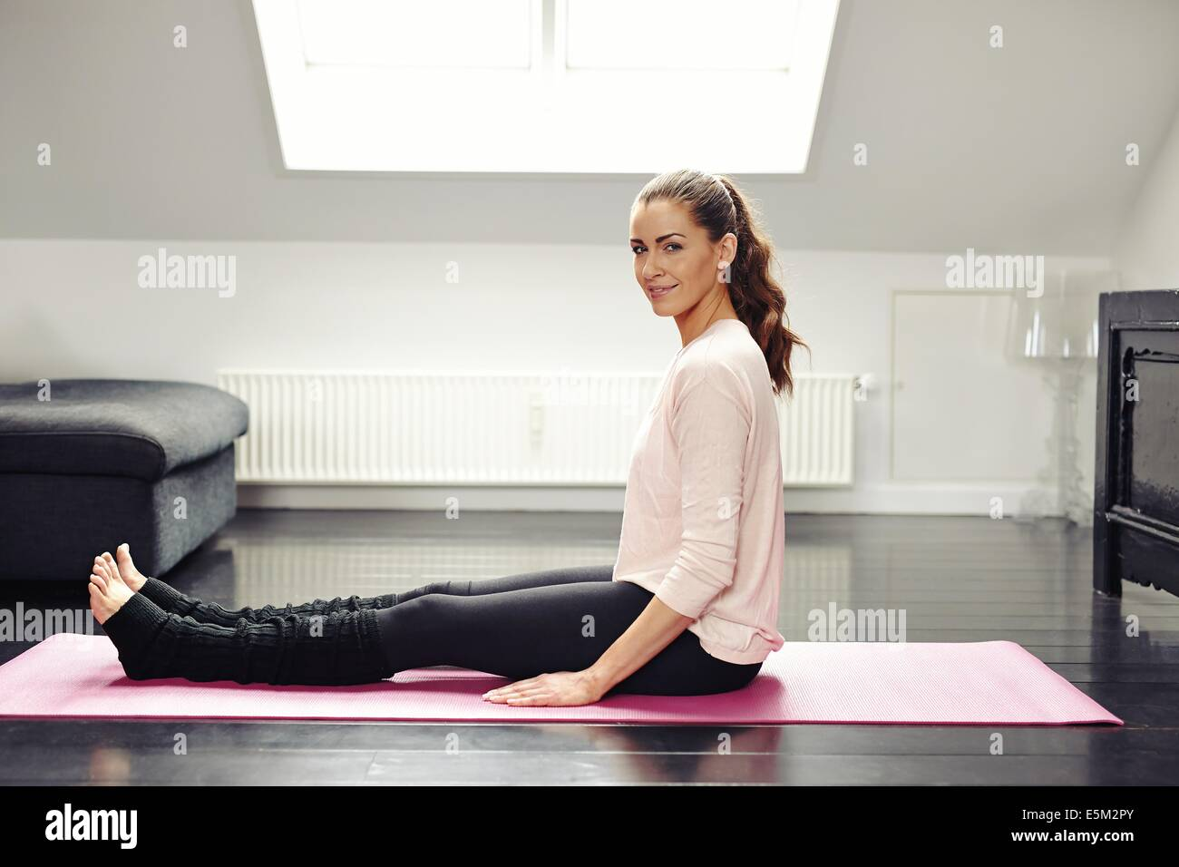 Portrait of fresh young woman sitting on exercise mat looking at camera smiling. Beautiful female exercising in - Stock Image