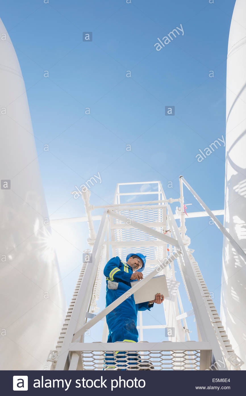 Male worker on platform at gas plant - Stock Image