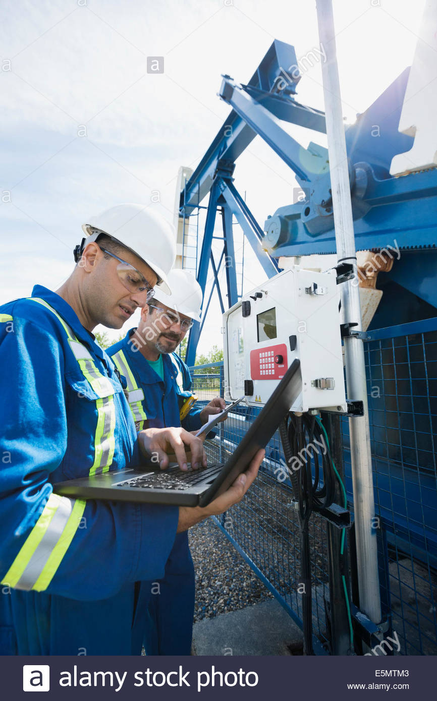 Male workers with laptop at oil well - Stock Image