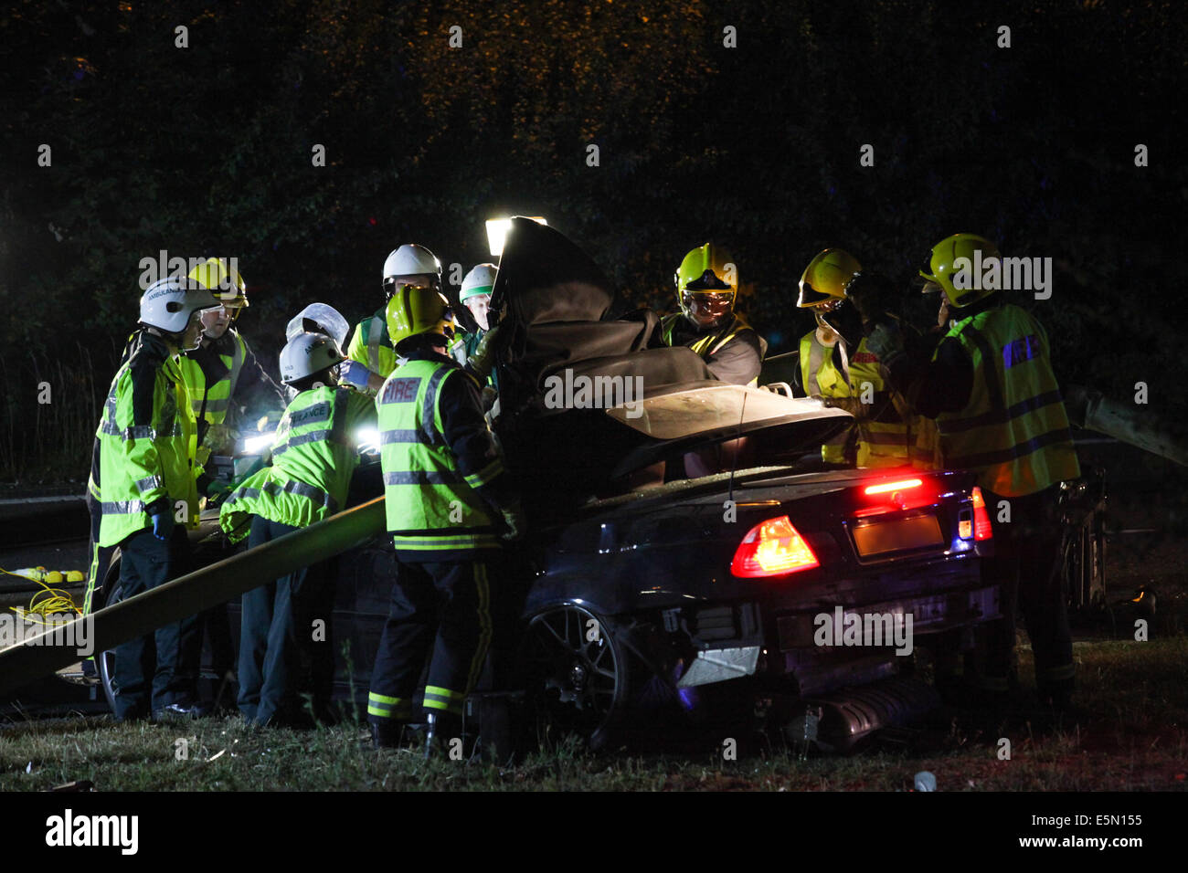Emergency services attempt to free a man from his BMW M3, which crashed into a large lamp post on the side of the - Stock Image