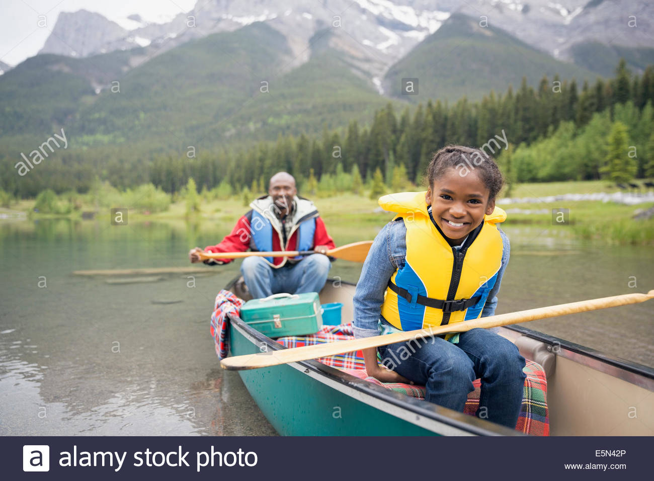 Father and daughter canoeing in lake - Stock Image