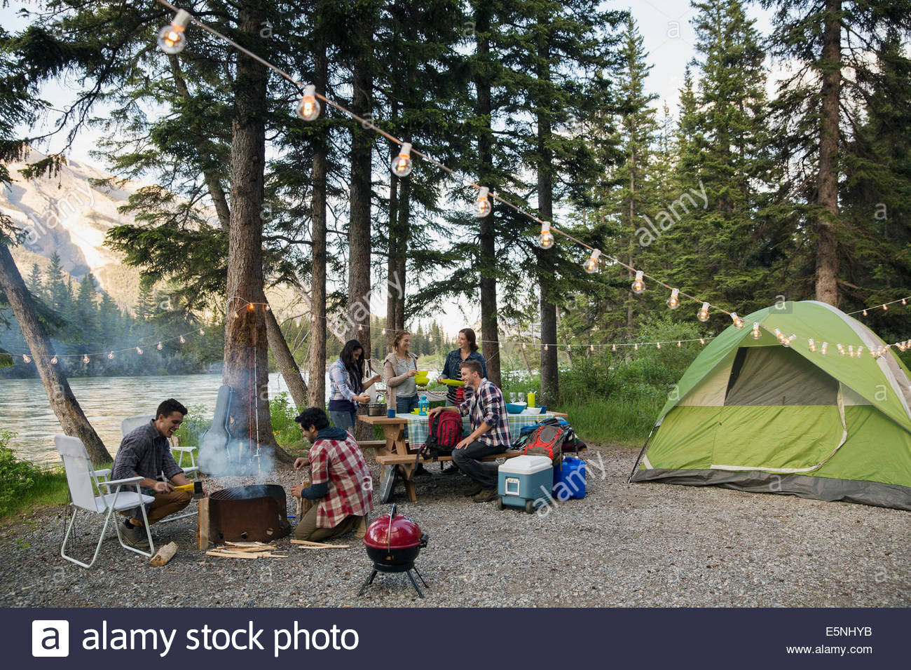 Friends hanging out at lakeside campsite - Stock Image