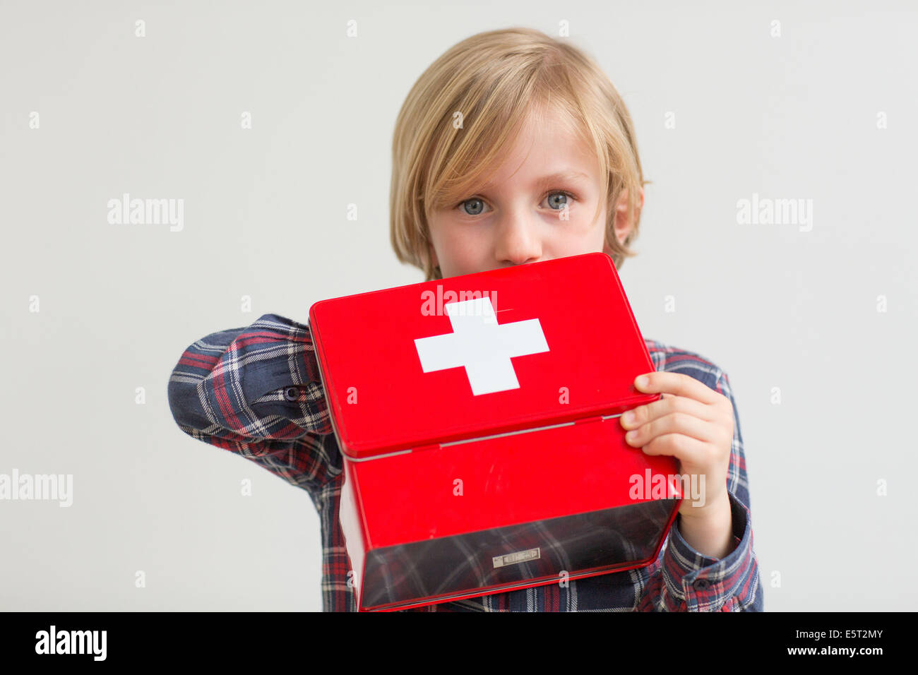 7 year old boy playing with drugs : poisoning hazard. - Stock Image