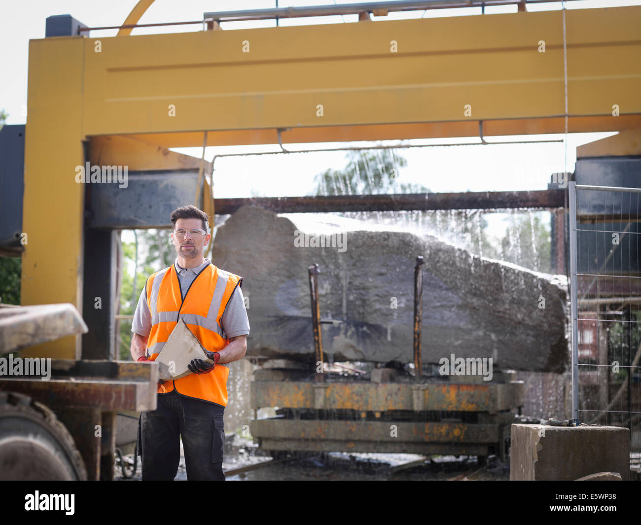 Portrait of quarry worker in front of large rock being cut in stone saw - Stock Image
