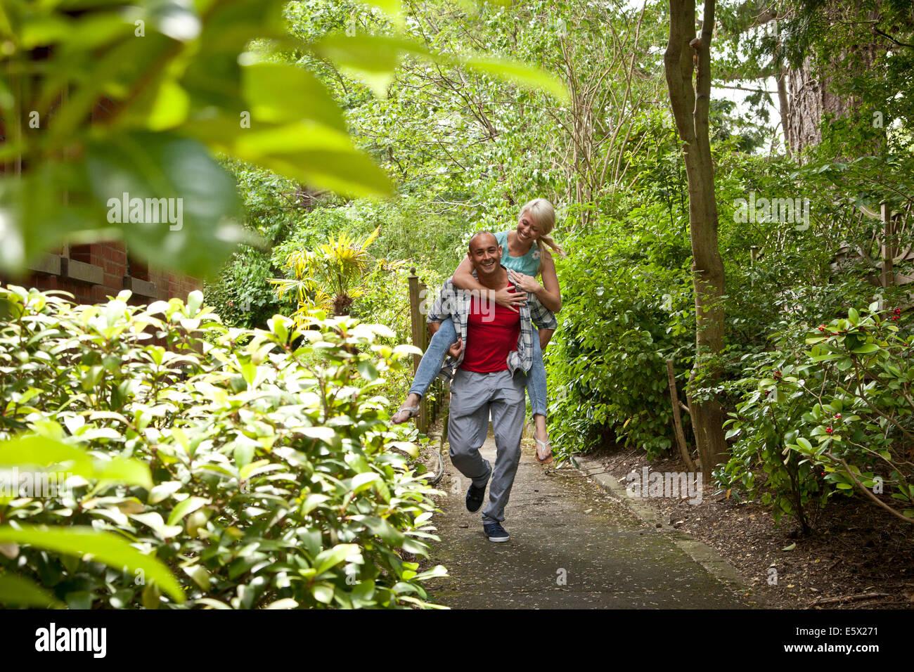 Happy couple having fun giving piggy back in garden - Stock Image