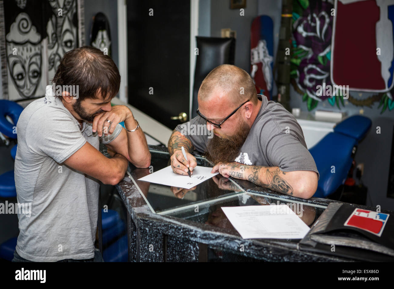 Artist drawing up tattoo ideas with a client - Stock Image