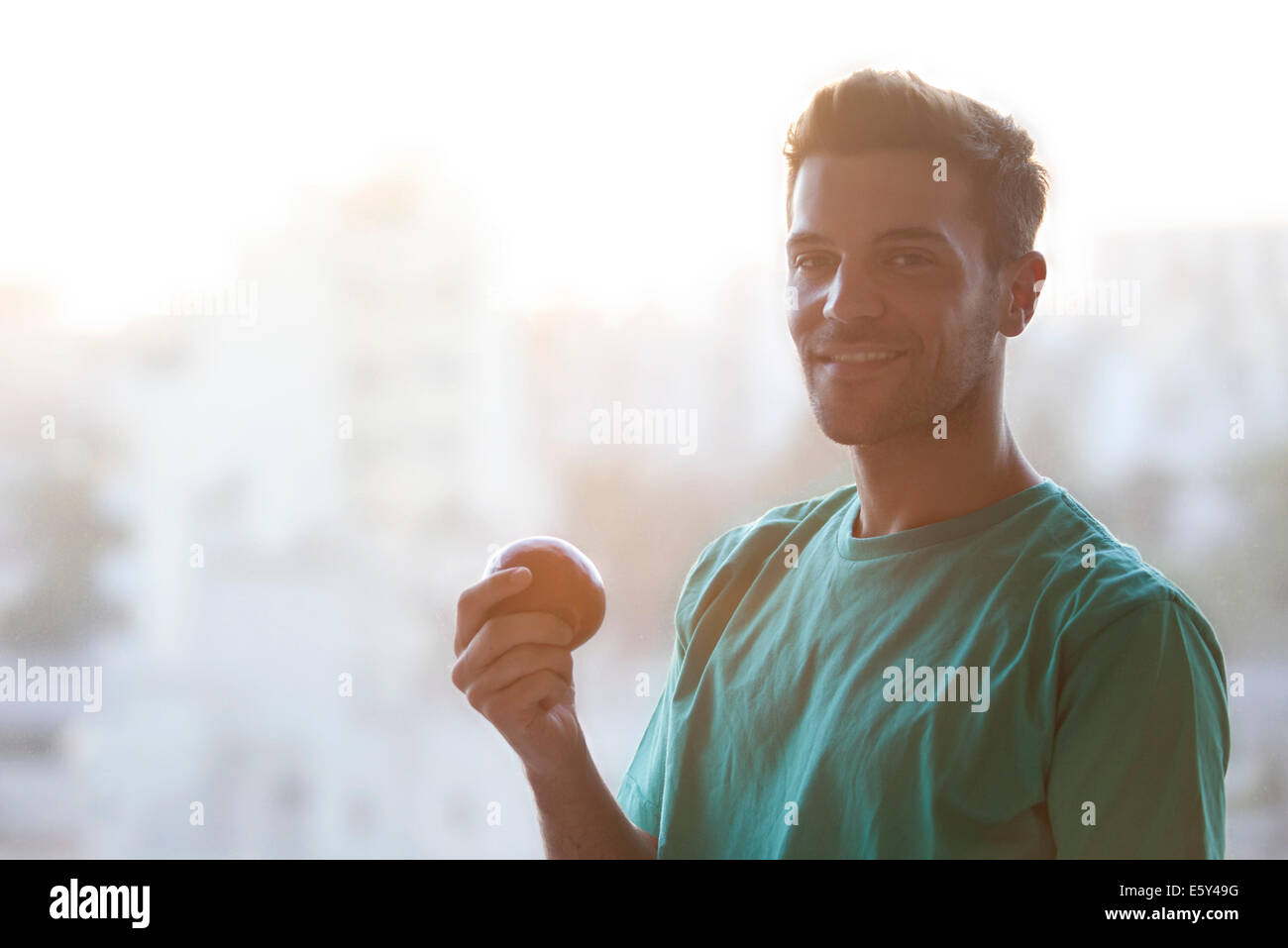 Man holding apple, portrait - Stock Image