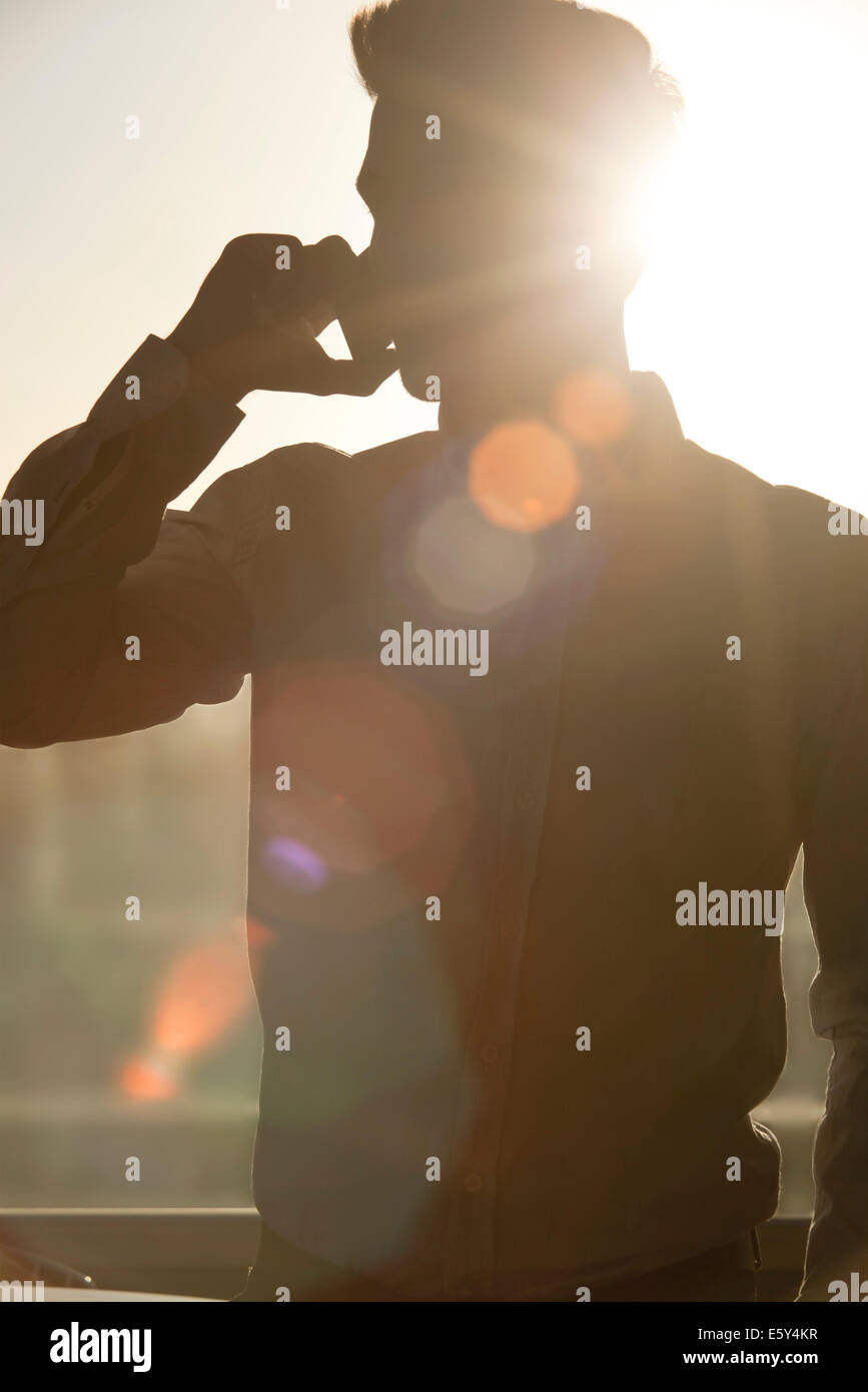 Man talking on cell phone, silhouetted by sun shining through window - Stock Image