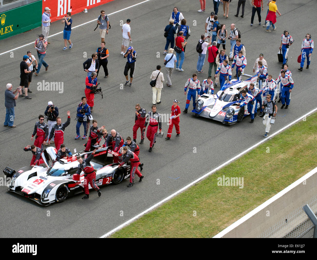 Audi and Toyota Hybrid racing cars on the way to the starting grid 2014 Le Mans - Stock Image