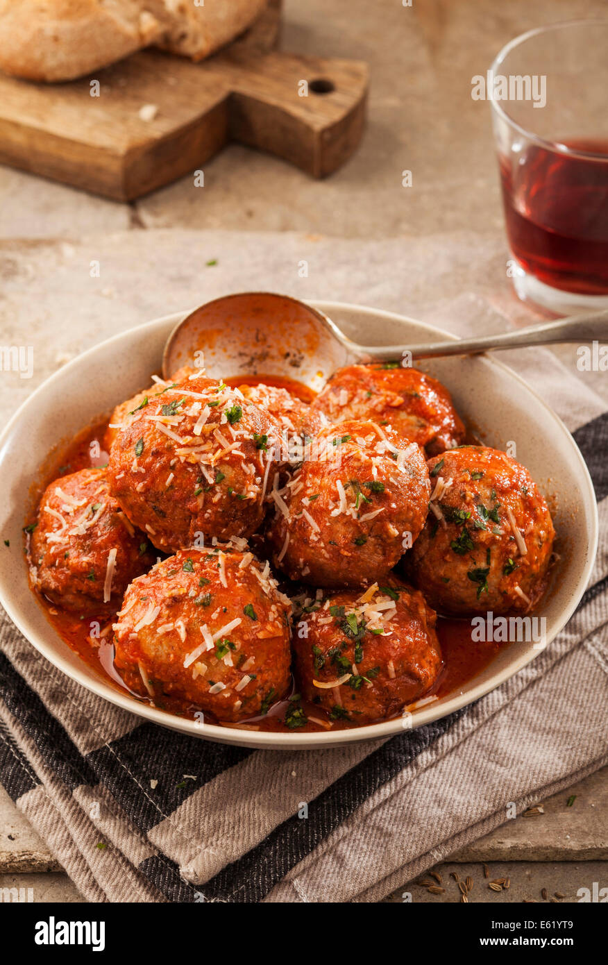 Meatballs cooked in tomato sauce in bowl on grey backround - Stock Image