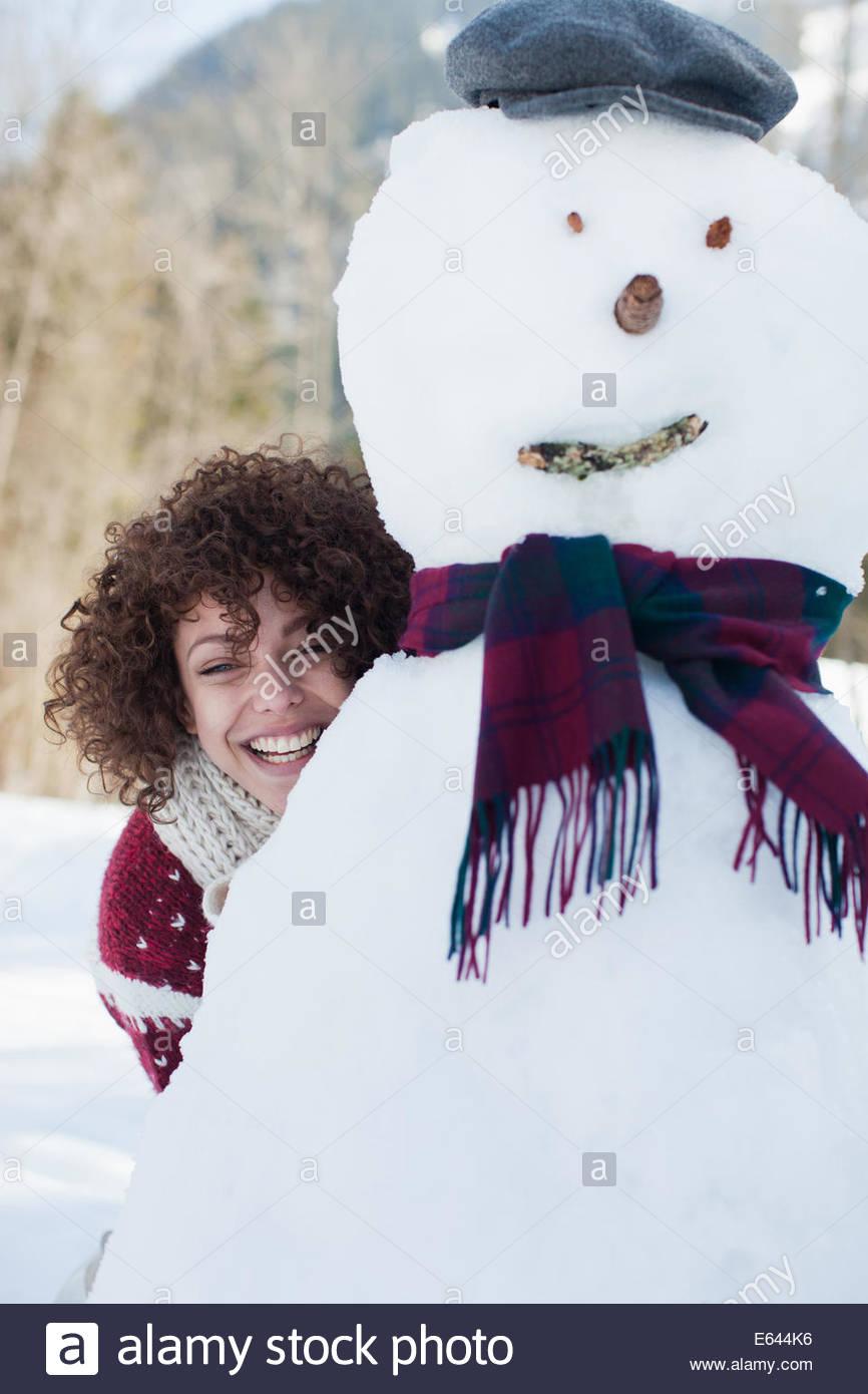 Woman hiding behind snowman - Stock Image