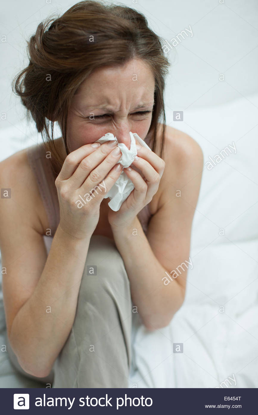 Sick woman in bed blowing nose - Stock Image