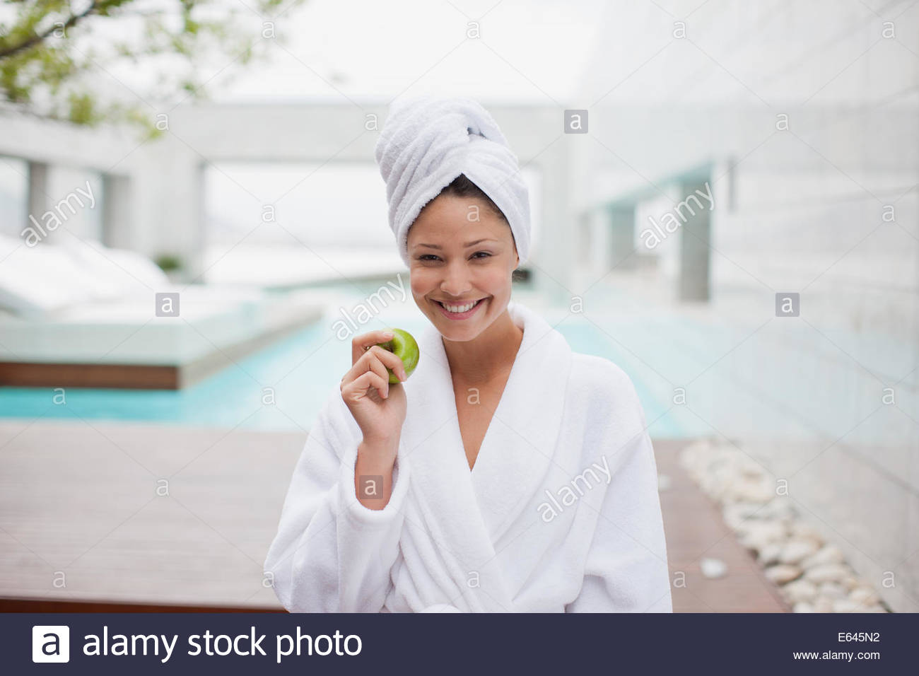 Woman with head wrapped in towel eating apple at poolside - Stock Image