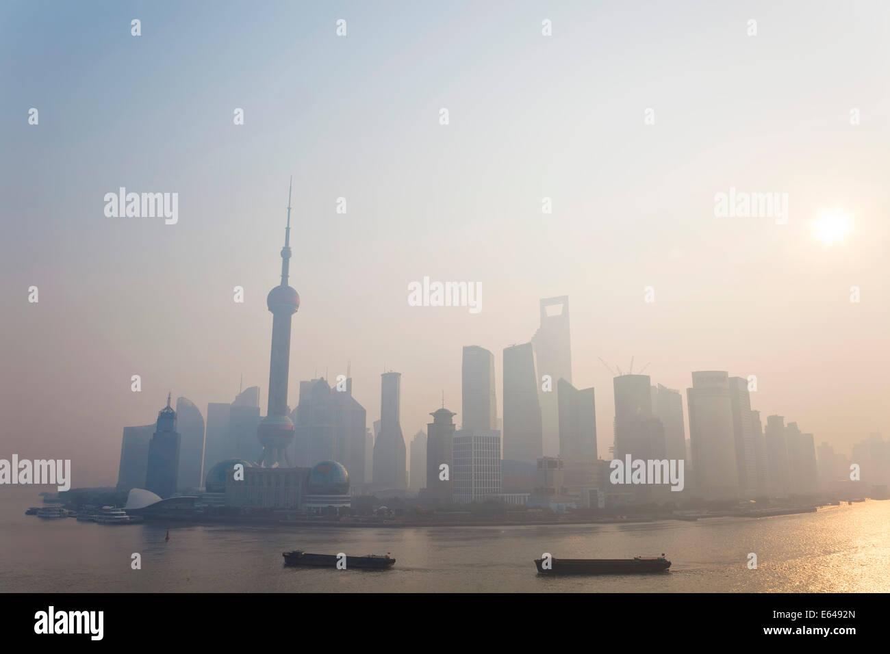 Sunrise over Pudong skyline & barges on Huangpu River, Shanghai, China - Stock Image