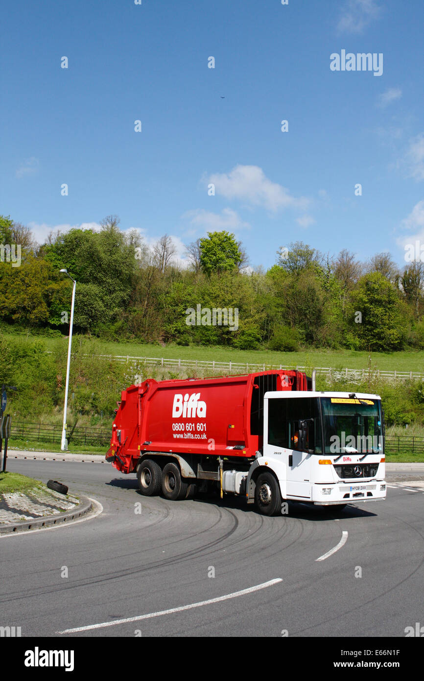 A refuse truck traveling around a roundabout in Coulsdon, Surrey, England - Stock Image