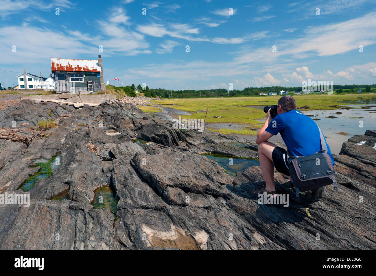 photographer-taking-a-picture-of-an-old-fisherman-shack-in-pointe-E6E0GC.jpg