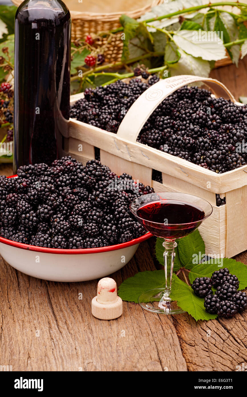 Ripe blackberries in bowl and fruit box and a bottle of blackberry liqueur with a glass Stock Photo