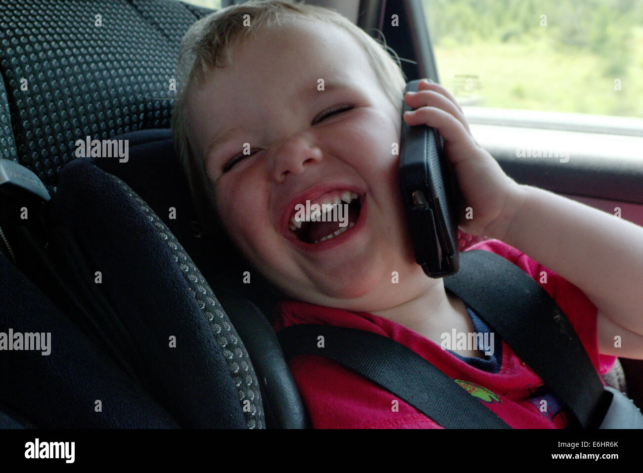 a-baby-in-a-car-seat-laughing-pretending-to-use-an-iphone-E6HR6K.jpg