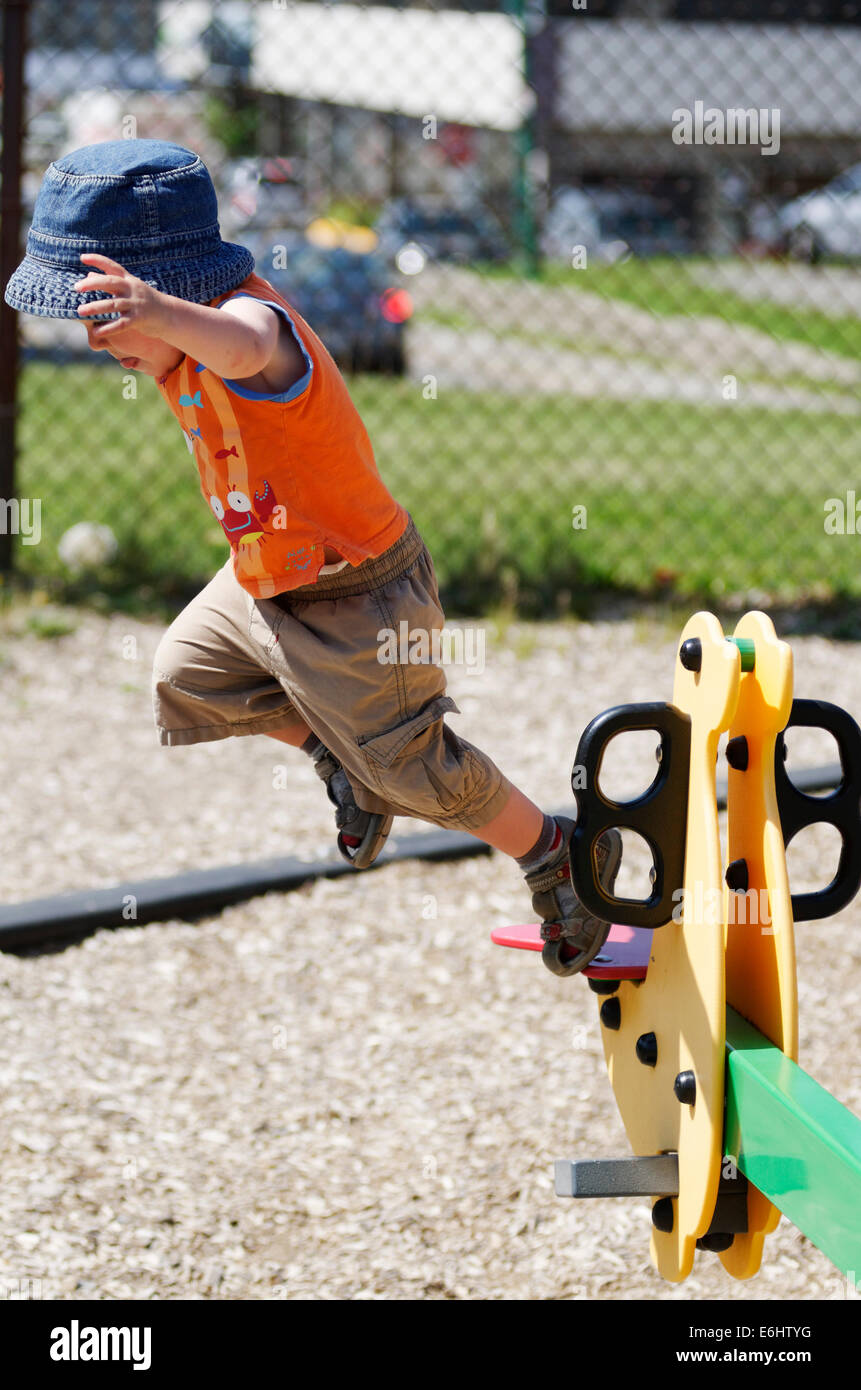 A two year old boy jumping from a see saw - Stock Image