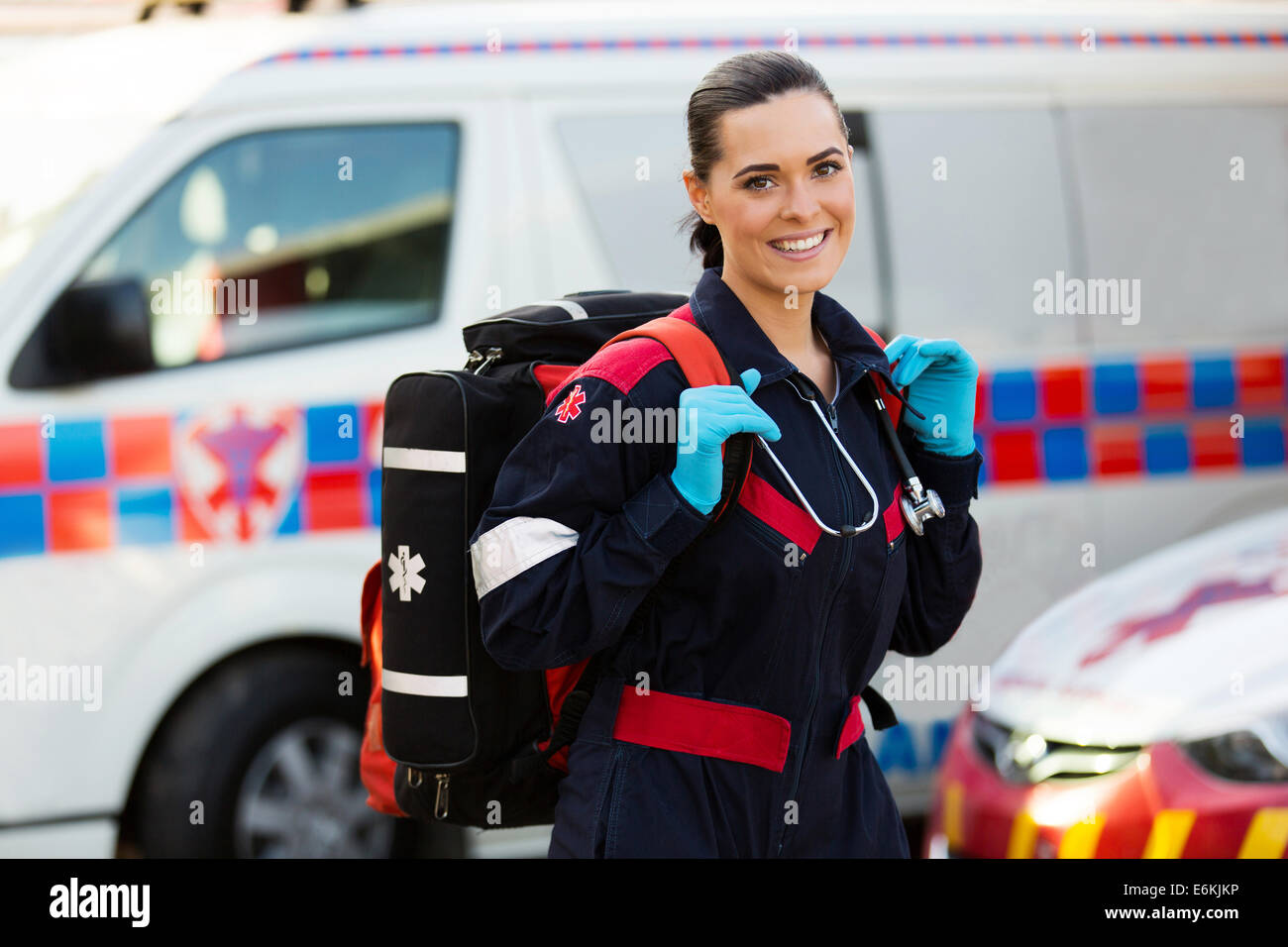 beautiful young female paramedic carrying lifepack in front of ambulance - Stock Image