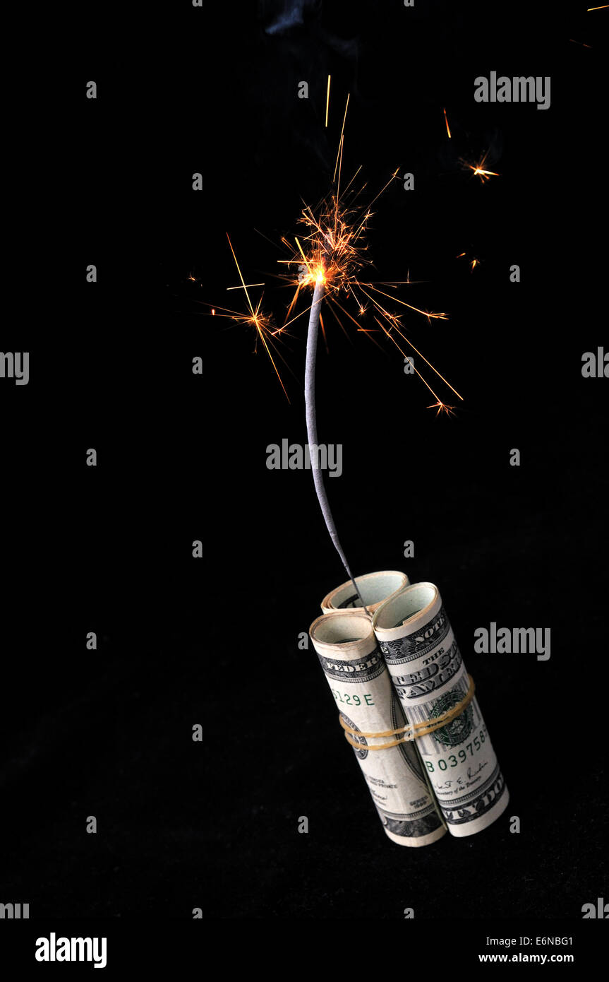 A roll of cash made into a dynamite stick has a lighted fuse throwing smoke and sparks before it explodes. - Stock Image