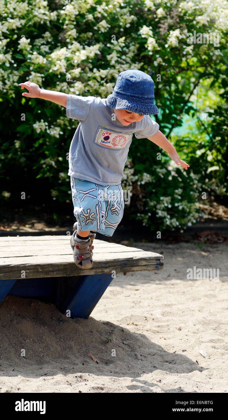A two year old boy jumping from a park bench - Stock Image