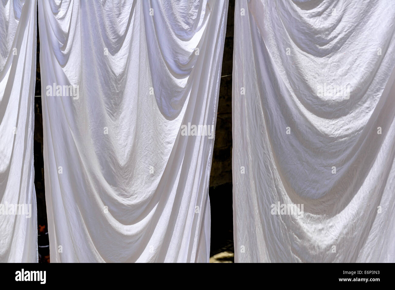 white-bedding-sheets-hanging-to-dry-on-a