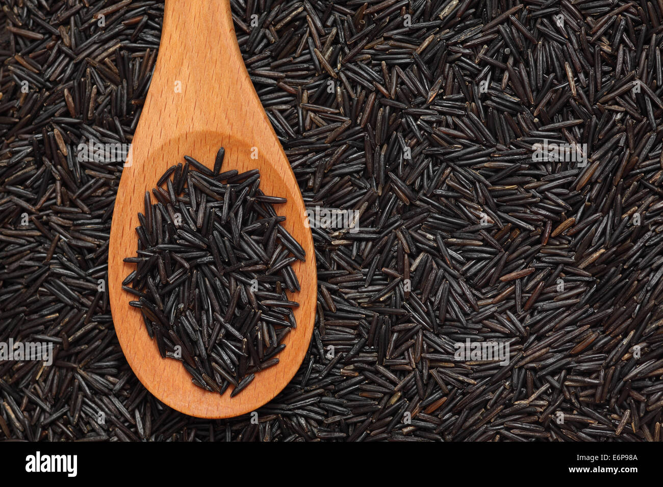 Wild rice in a wooden spoon on wild rice background. - Stock Image