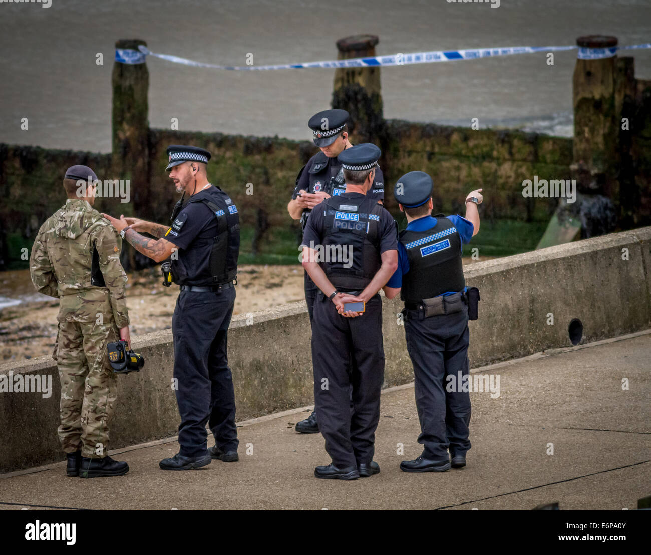 Bomb disposal and police at beach scene - Stock Image