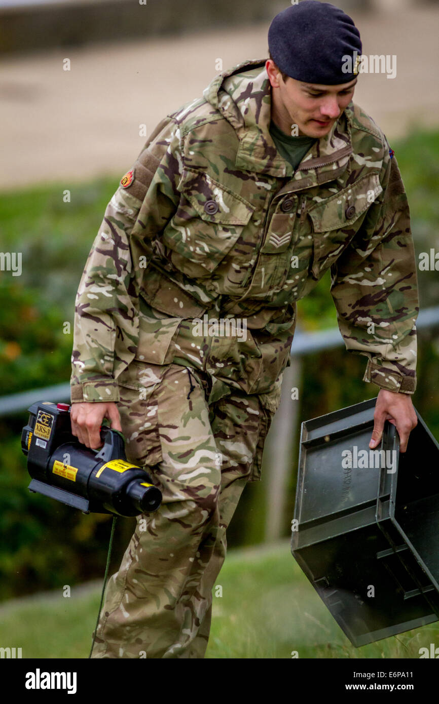 Royal logistics corps bomb disposal ammunition technician leaving a British beach scene carrying an XRS-3 x-ray - Stock Image