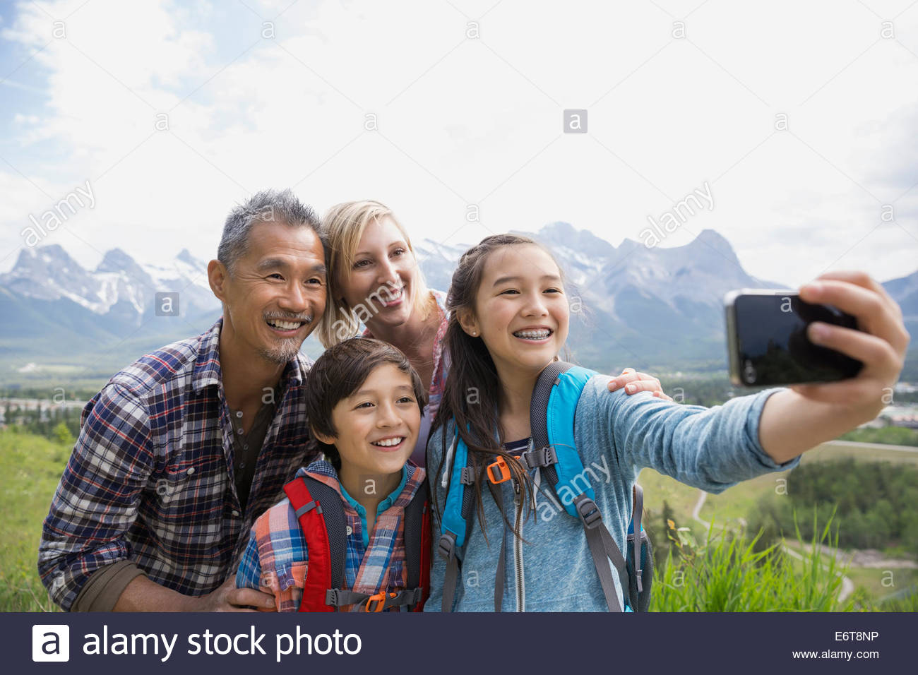 Family taking cell phone picture on rural hillside - Stock Image