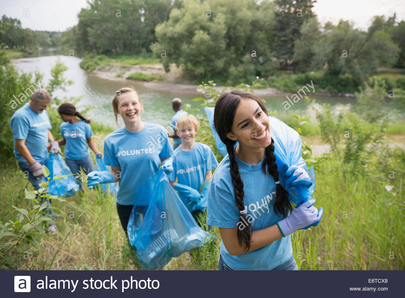 Volunteers carrying garbage bags in field - Stock Image