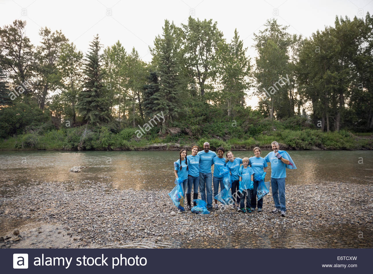Portrait of volunteers with garbage bags at riverbank - Stock Image