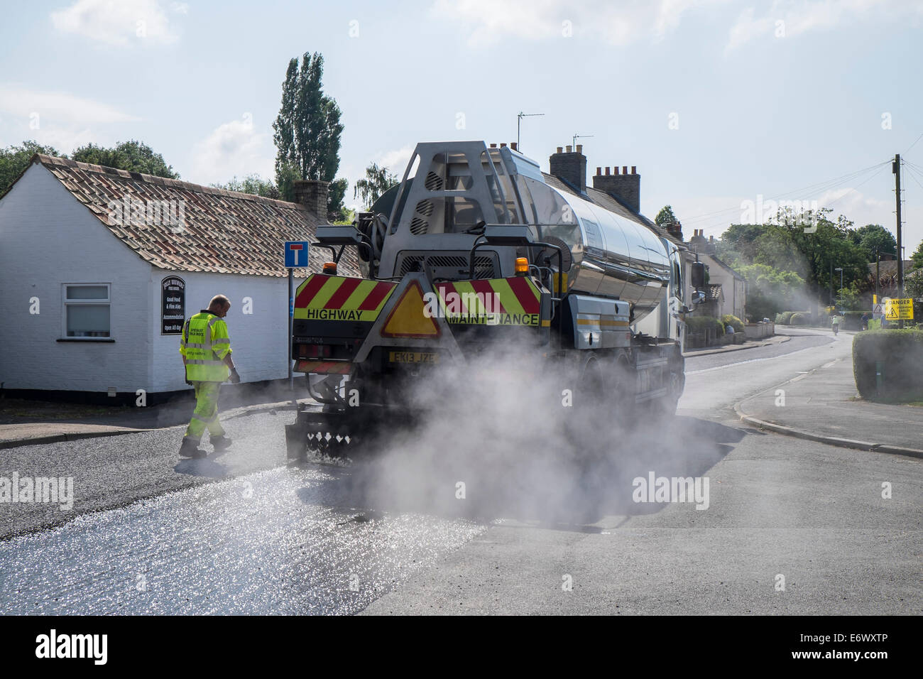 road-tar-tanker-spreading-hot-tar-to-take-chippings-fen-road-milton-E6WXTP.jpg