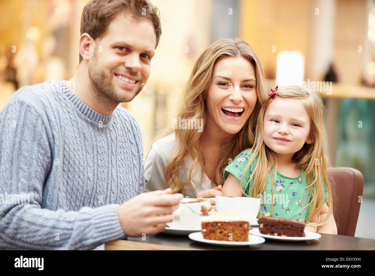 Family Enjoying Snack In Café Together - Stock Image