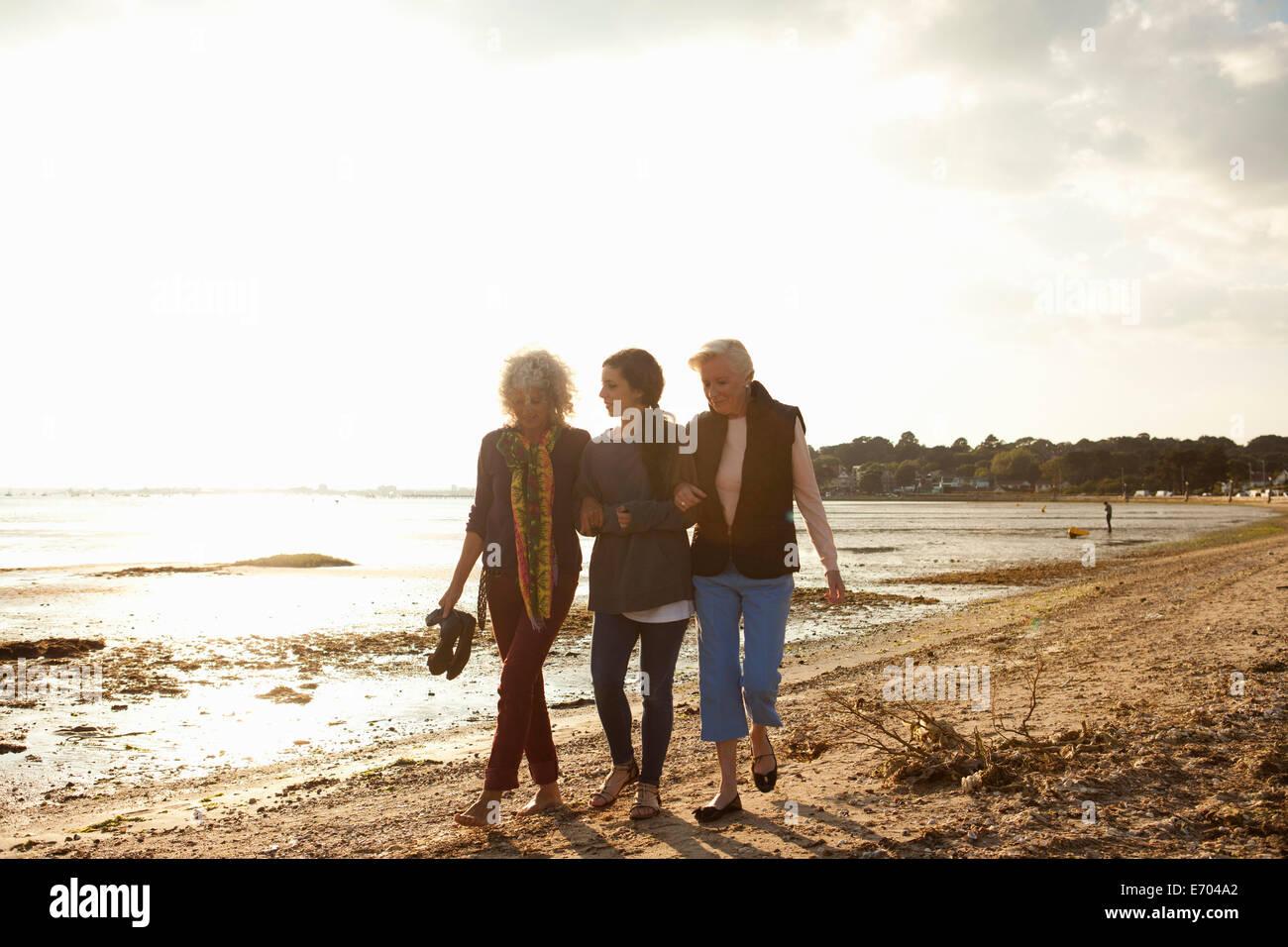 Female family members walking on beach - Stock Image