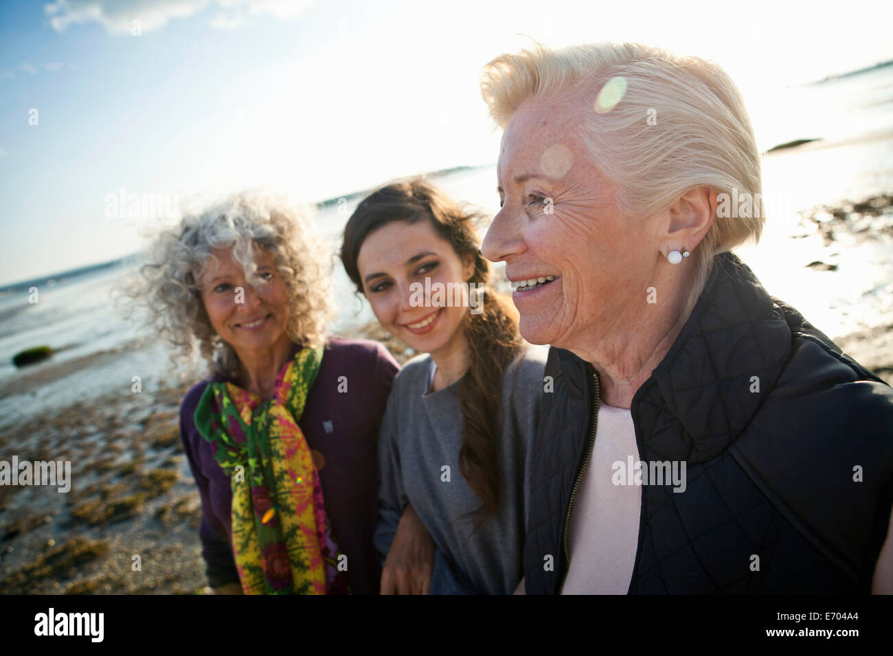 Female family members chatting on beach - Stock Image