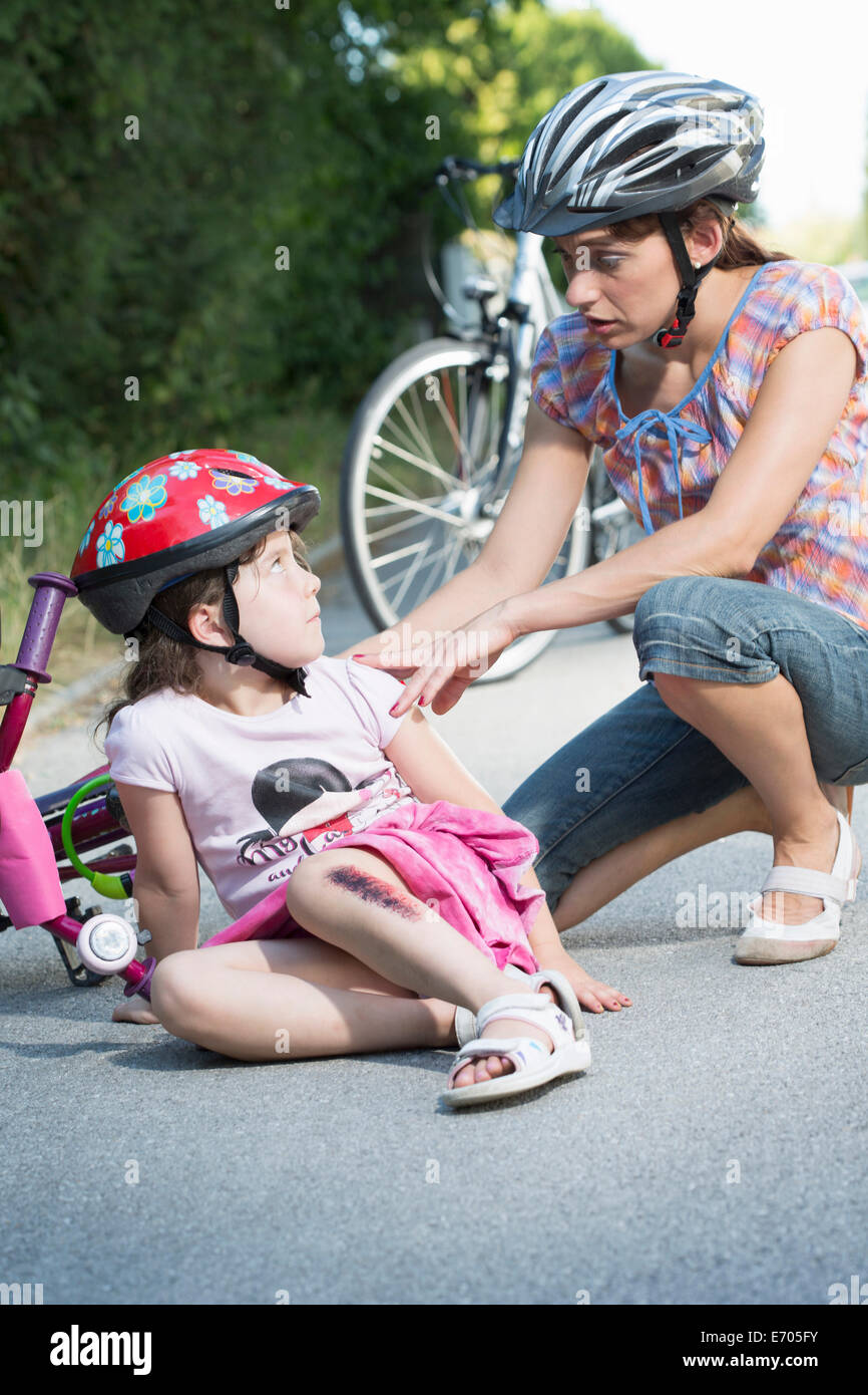 Mother caring for daughter fallen off bicycle - Stock Image