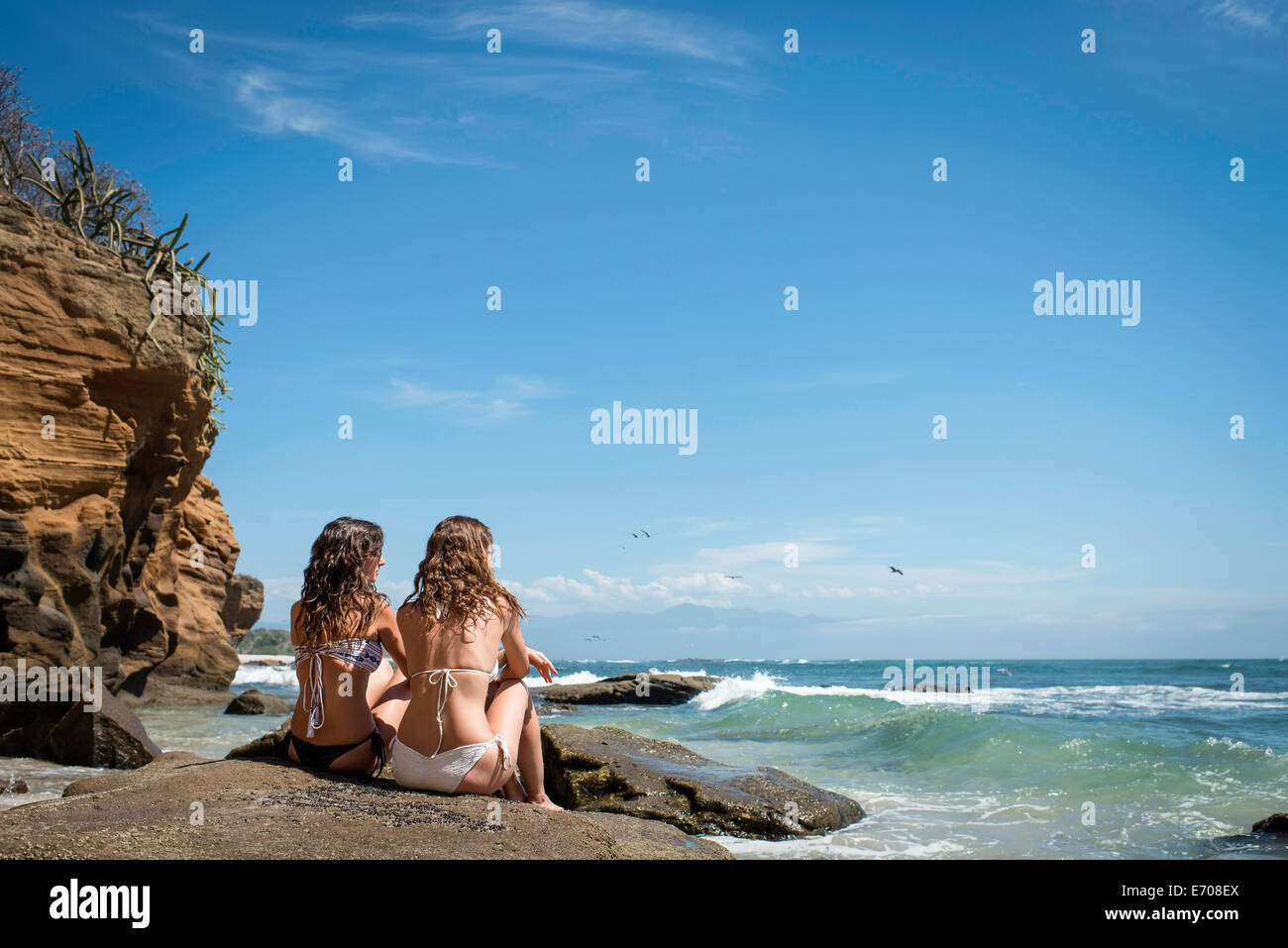 Two young women sitting on rocks, looking out to ocean - Stock Image