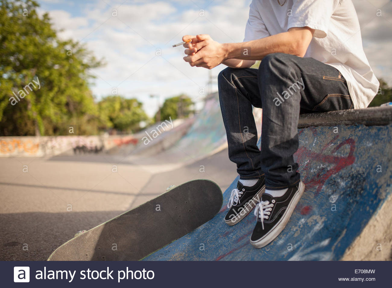 Cropped shot of young male skateboarder smoking cigarette in city skateboard park - Stock Image