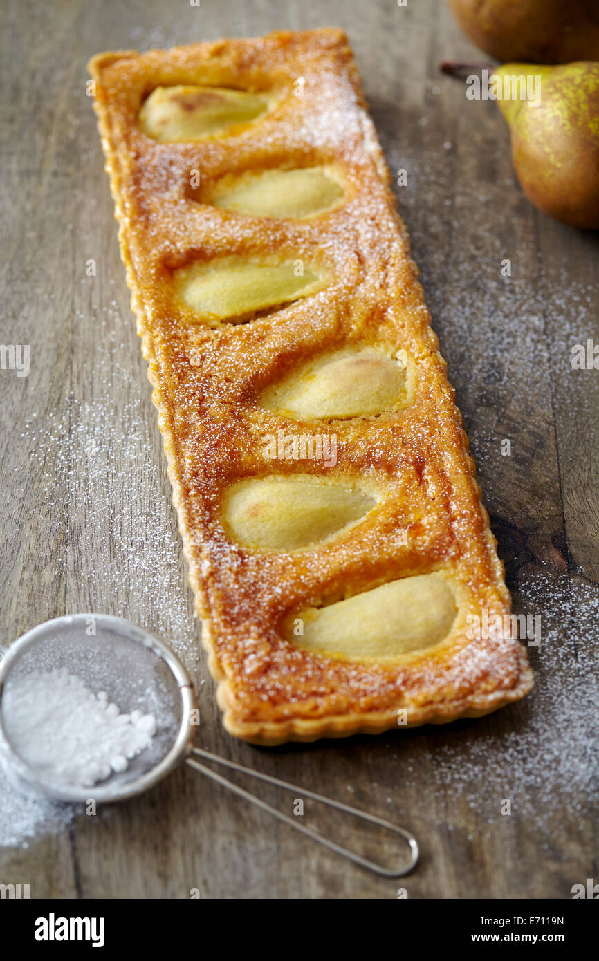 Pear tart sprinkled with icing sugar - Stock Image