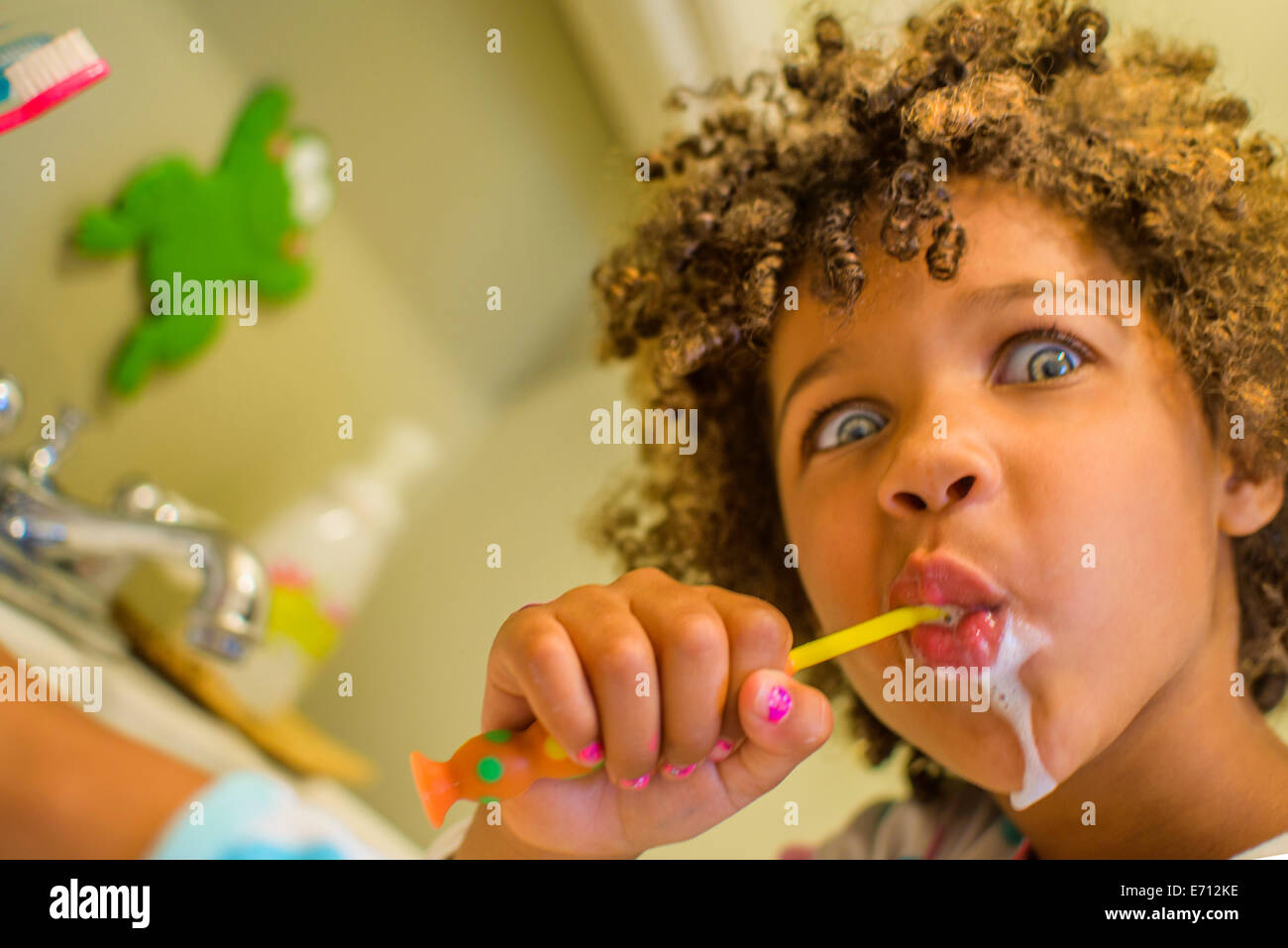 Portrait of girl pulling face whilst brushing teeth - Stock Image