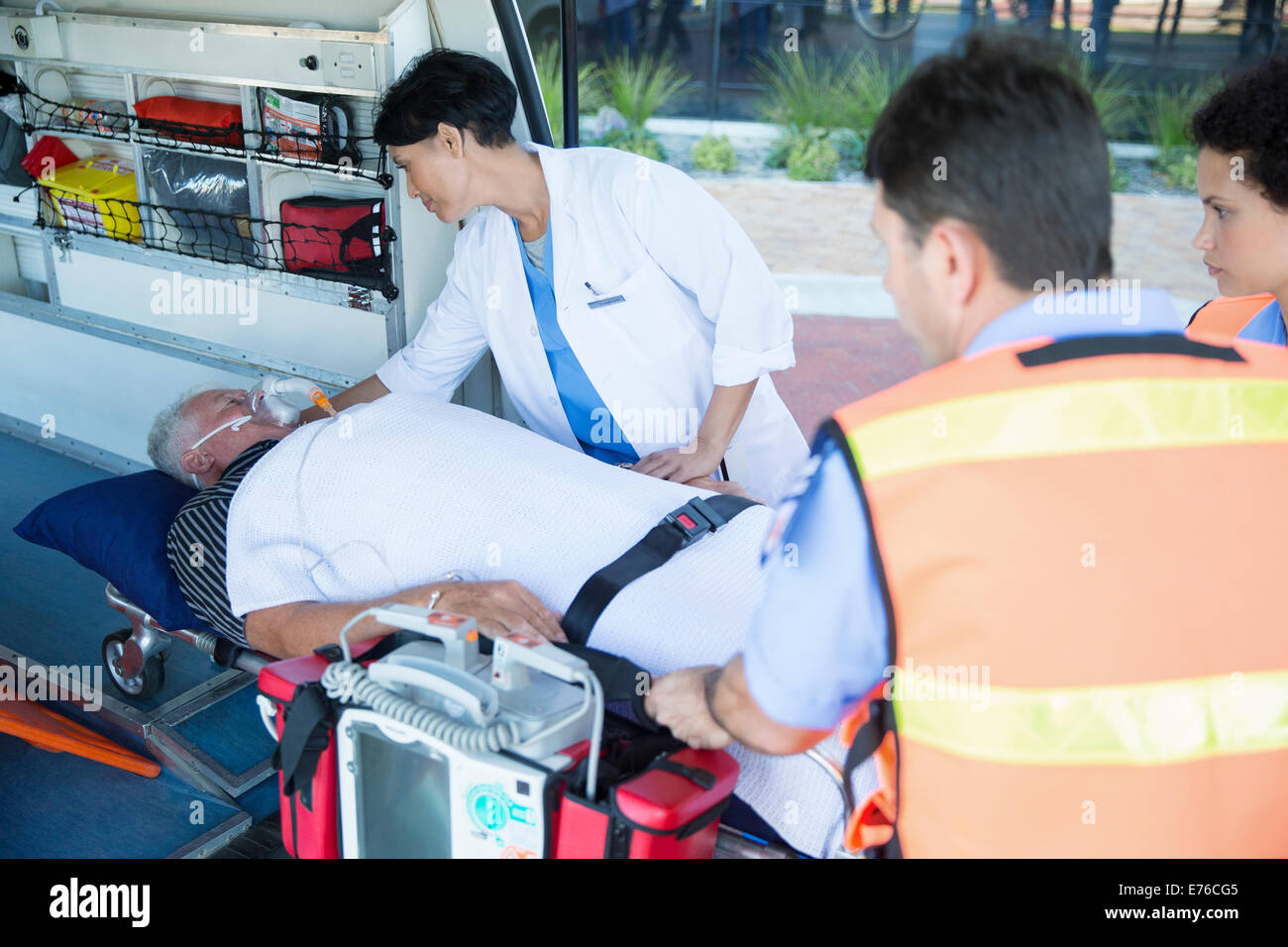 Doctor examining patient on ambulance stretcher - Stock Image