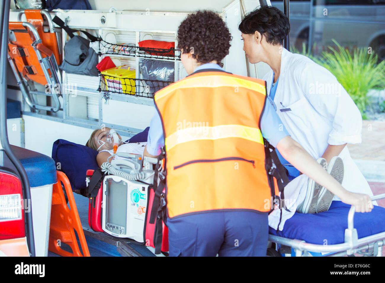 Paramedics wheeling patient out of ambulance - Stock Image