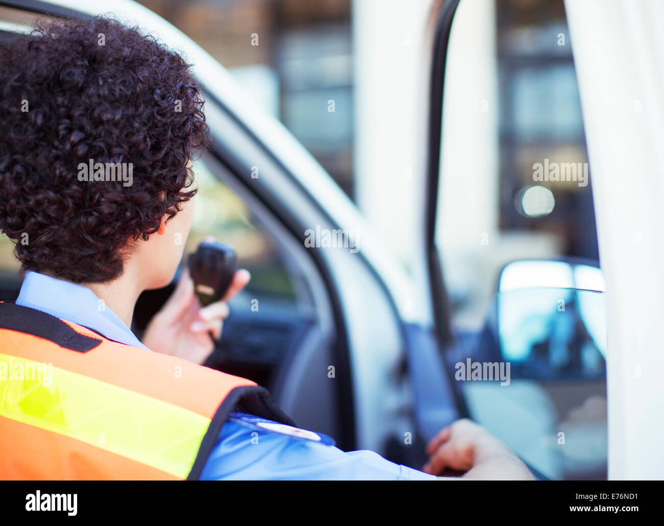 Paramedic using walkie talkie in ambulance - Stock Image