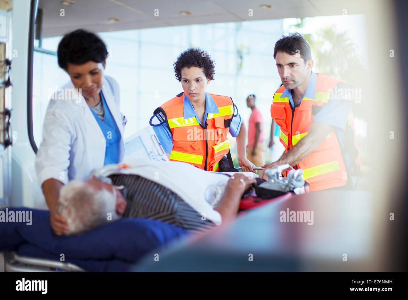 Paramedics and nurse examining patient in ambulance - Stock Image