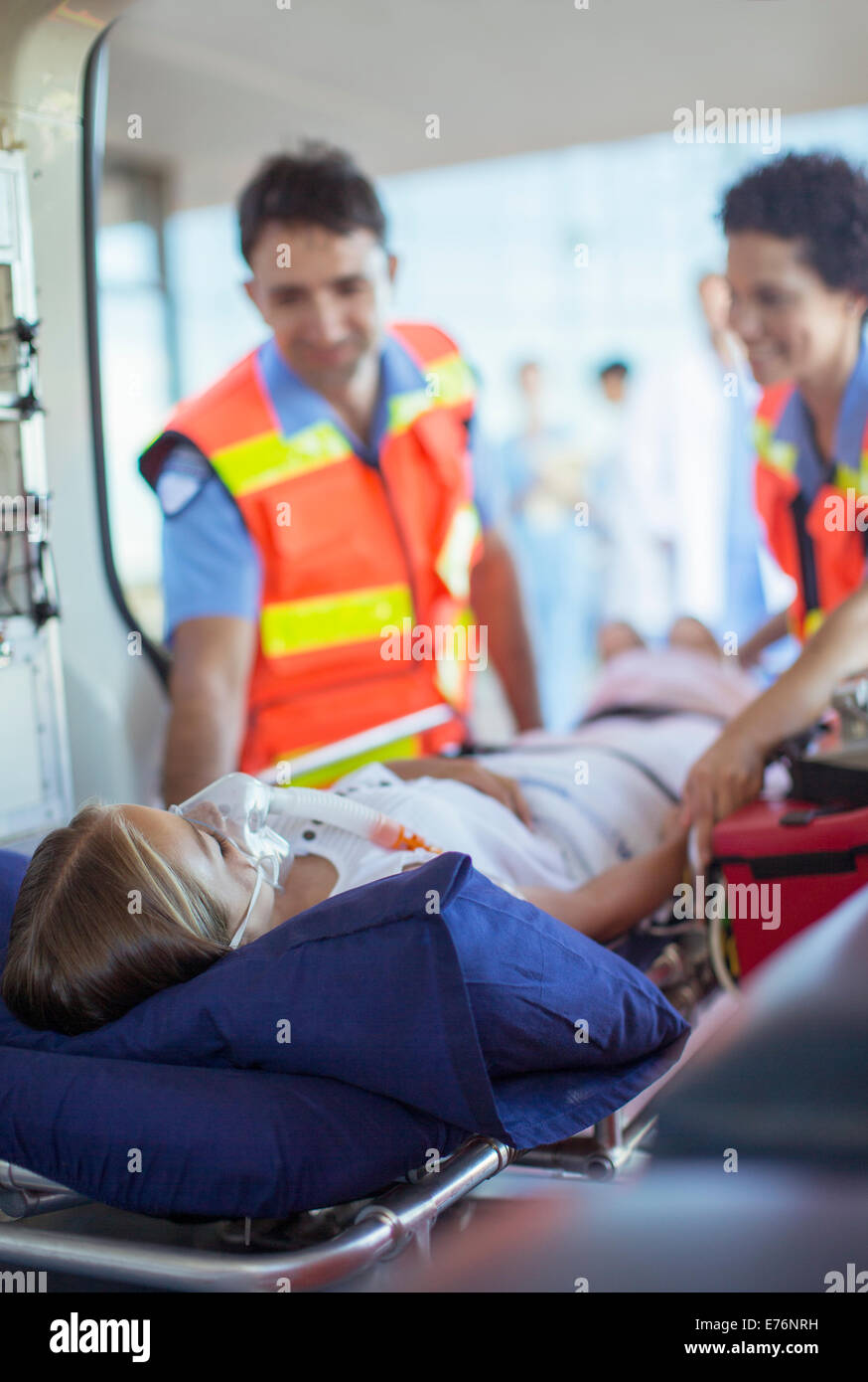 Paramedics examining patient on ambulance stretcher - Stock Image