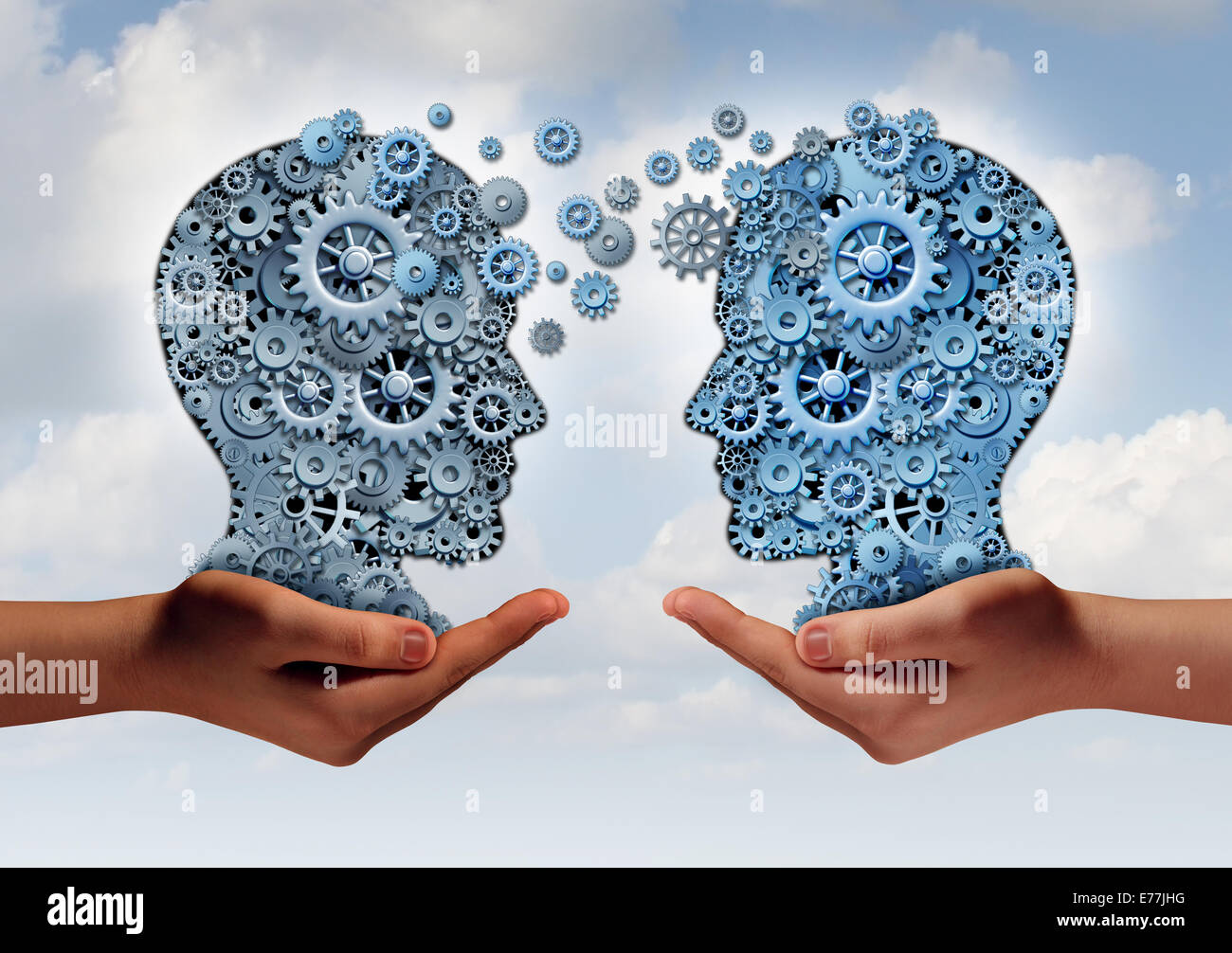 Business technology concept as two hands holding a group of  machine gears shaped as a human head as a symbol and - Stock Image