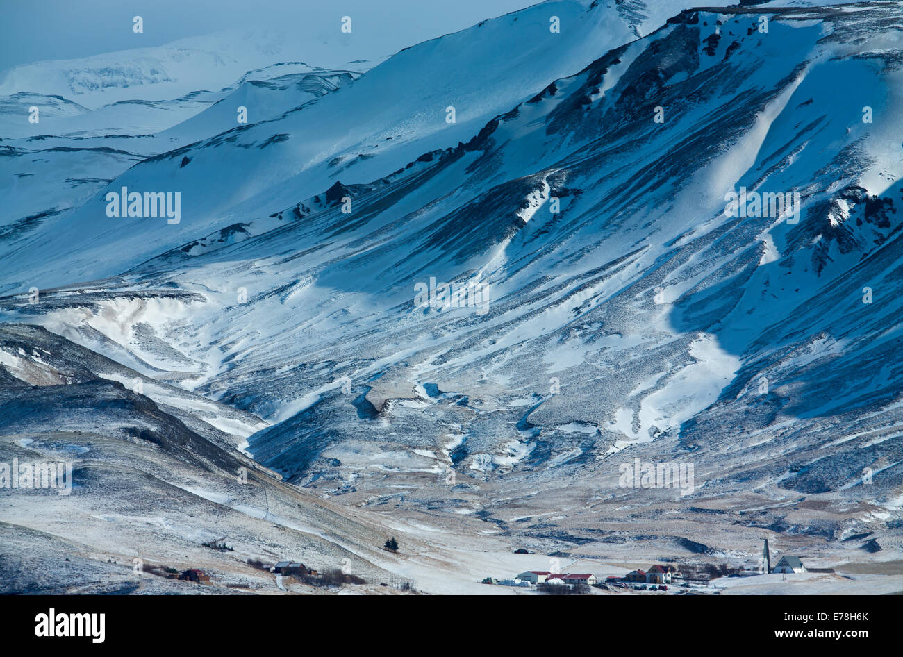 farmhouses dwarfed by the icy mass of Eyjafjallajökull, southern Iceland - Stock Image
