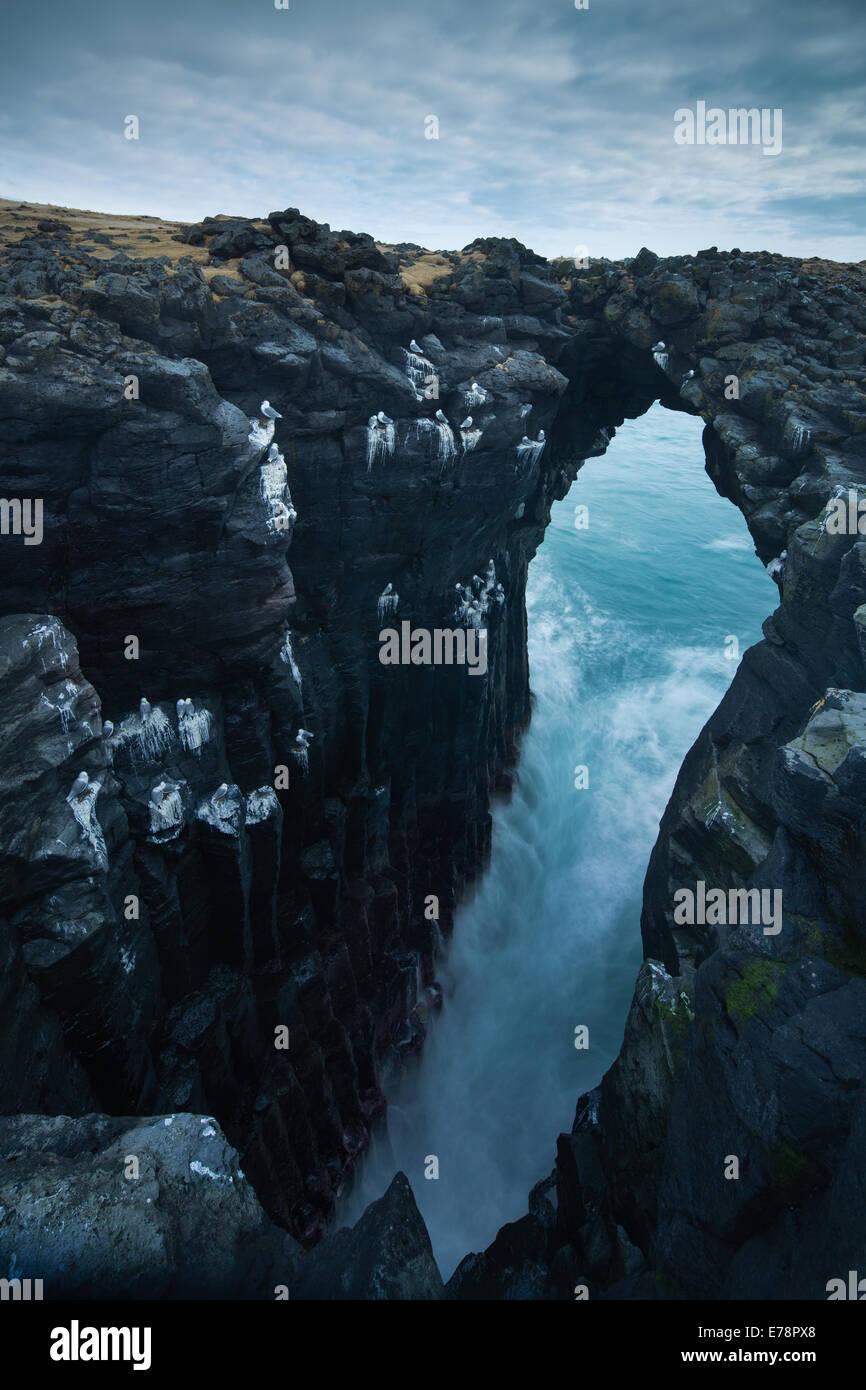 sea cave streaked with the guano of fulmars and kittiwakes, nr Arnastapi, Snaefellsnes Peninsula, western Iceland - Stock Image